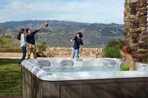 Family throwing a football near their Sundance Spas hot tub.