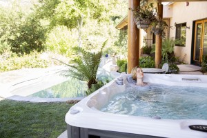 woman relaxing in her backyard hot tub