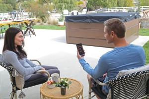 Man and woman using the SmartTub App in their backyard.