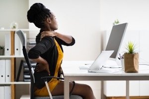 Woman with back pain sitting at a desk.